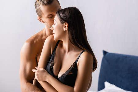 Sexy man kissing girlfriend in black lace bra in bedroom