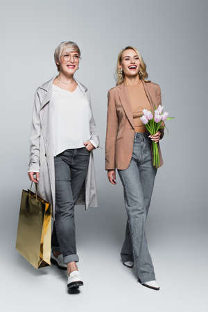 happy, stylish mother and daughter walking with shopping bag and tulips on gray