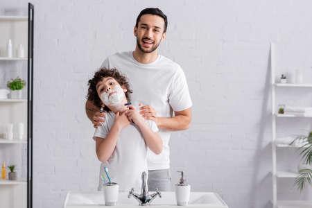 Boy in shaving foam holding razor near smiling father