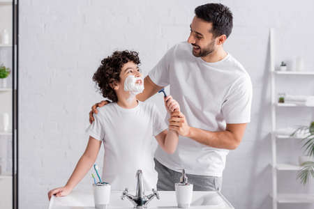 Muslim boy with shaving foam on face holding razor and looking at father Stock Photo