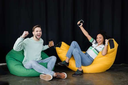 young, successful business people showing win gesture while sitting in bag chairs