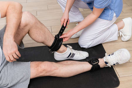 cropped view of trainer fastening leather belt on leg of man in rehabilitation center