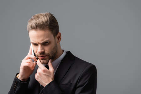 pensive businessman touching chin while talking on cellphone isolated on gray Foto de archivo
