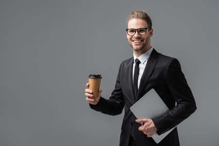 happy businessman with takeaway drink and laptop smiling at camera isolated on gray