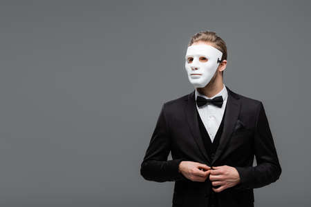 businessman in face mask buttoning blazer isolated on gray Archivio Fotografico