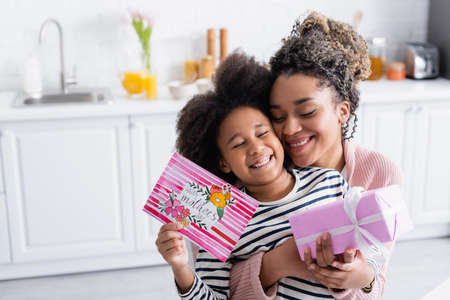 excited african american woman embracing happy daughter holding gift box and happy mothers day card