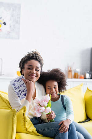 joyful african american girl sitting near happy mom holding tulips and happy mothers day card Imagens