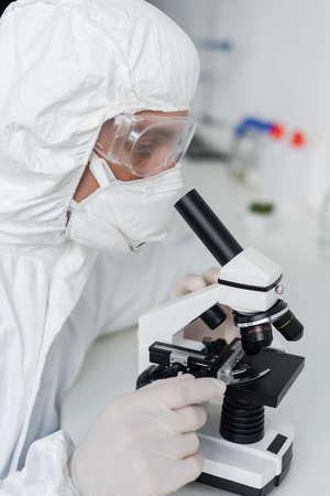 Scientist in latex gloves and goggles using microscope in laboratory Standard-Bild