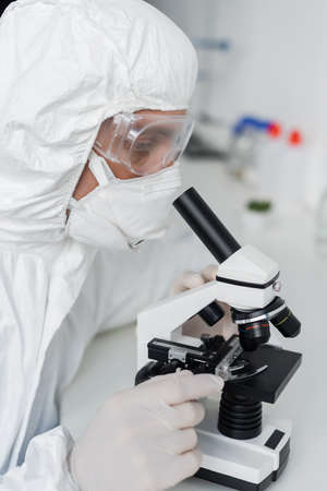 Scientist in latex gloves and goggles using microscope in laboratory Stock fotó