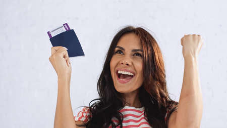 excited woman holding passport with air ticket