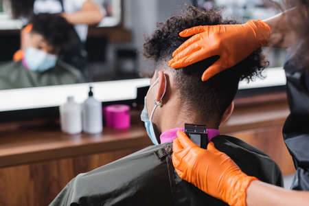 African american hairdresser trimming neck of man in medical mask Stock Photo