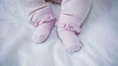 cropped view of baby in romper and socks in bed Archivio Fotografico