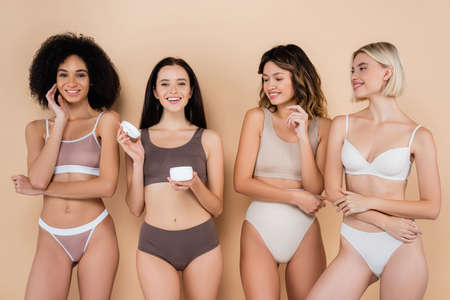 happy woman holding body cream near multicultural friends on beige