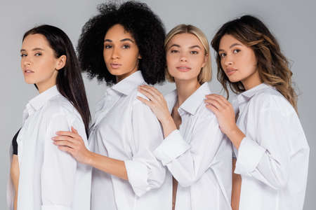 young interracial women in white shirts looking at camera on gray Zdjęcie Seryjne