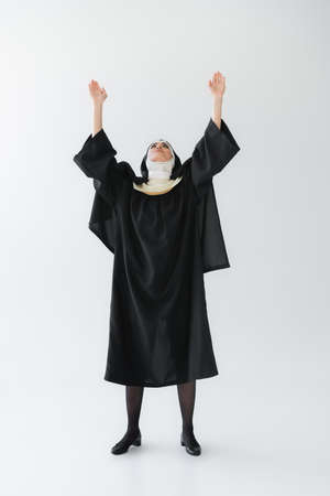 full length view of nun in black vestment praying with raised hands on gray background