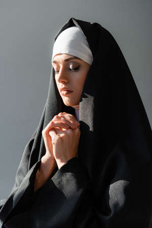 young nun praying with closed eyes isolated on gray