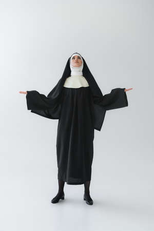 full length view of young nun looking up while praying with open arms on gray background