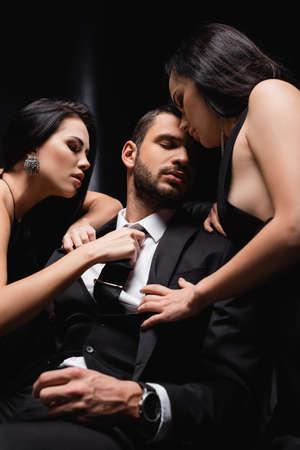 sensual women undressing businessman in suit on black