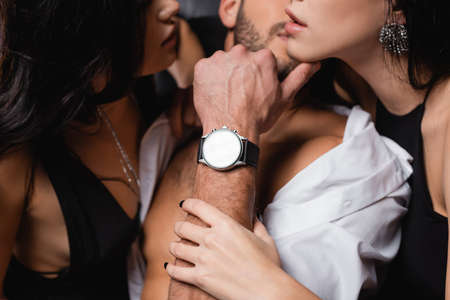 partial view of passionate women seducing young man on blurred background
