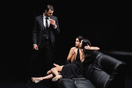 man in suit near women embracing on leather couch on black background Banque d'images
