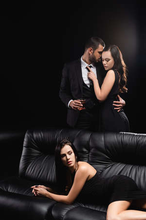 brunette woman lying on leather couch near lovers embracing on black background