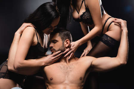 women in underwear touching face of muscular man on black background Banque d'images