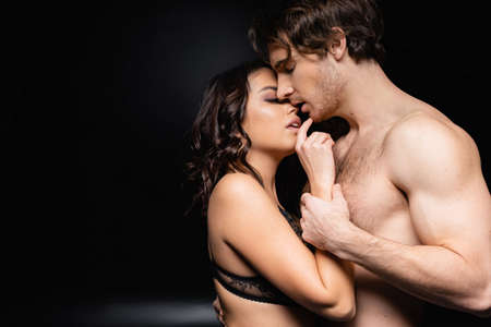 woman and shirtless man hugging on black Banque d'images