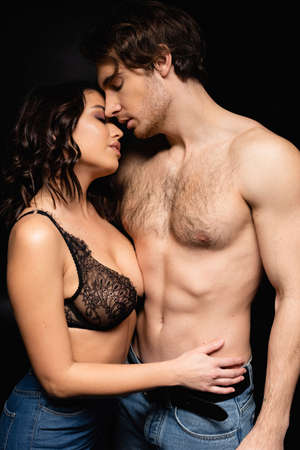 brunette woman in lace bra hugging with shirtless man isolated on black Standard-Bild