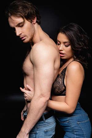 woman in lace bra hugging shirtless man on black