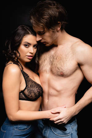 woman in lace bra holding hands with shirtless man isolated on black