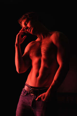 red lighting on body of muscular man standing with hand in pocket isolated on black Foto de archivo