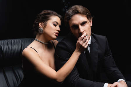 seductive woman holding cigarette near man in suit isolated on black