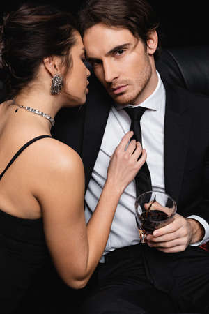 woman in slip dress seducing man in suit holding glass of whiskey on black