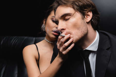 blurred seductive woman holding cigarette near man in suit on black