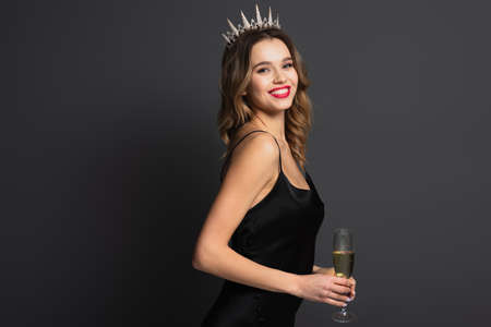 happy young woman in black slip dress and tiara holding glass of champagne on gray Foto de archivo