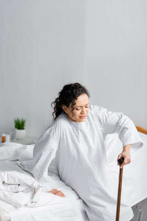 african american woman leaning on walking stick while getting up from hospital bed