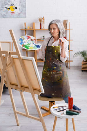 mature artist holding paintbrush and palette while standing near canvas