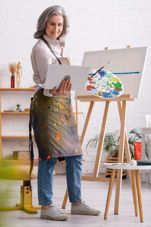 happy mature woman holding palette and laptop while watching tutorial near canvas