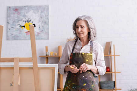 pleased middle aged artist in apron with spills holding paintbrush and looking at canvas on easel