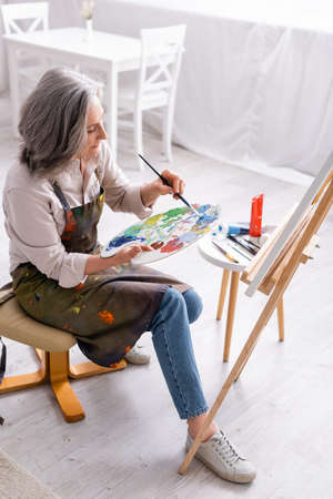 high angle view of middle aged woman holding paintbrush and palette with colorful paints