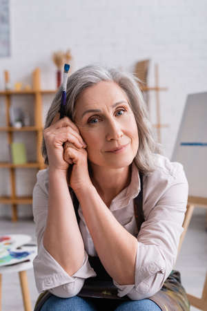 pleased middle aged painter with gray hair holding paintbrush