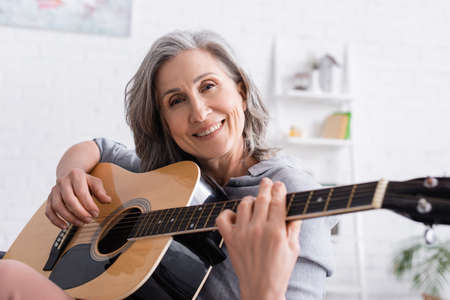 smiling mature woman with gray hair playing acoustic guitar at home Stockfoto