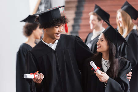 African american graduate hugging asian friend with diploma