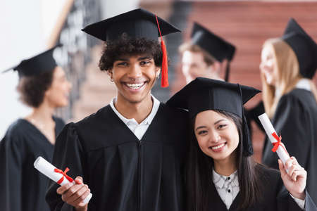 African american bachelor with diploma smiling near asian friend