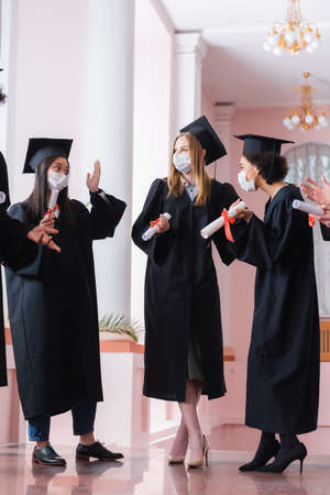 Multiethnic graduates in medical masks holding diplomas and talking in hall of university