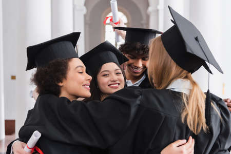 Cheerful asian graduate looking at camera while hugging friends