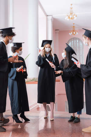 Asian bachelor in protective mask holding diploma near multiethnic friends