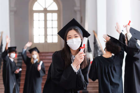 Asian bachelor in cap and medical mask holding diploma near blurred friends