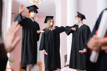 African american graduate in medical mask waving hand near friends doing embow bump