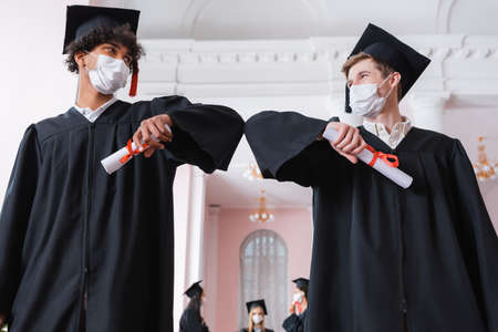 Low angle view of interracial bachelors in medical masks doing elbow bump while holding diplomas